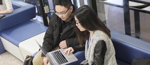 Two students working on a laptop in a lounge area