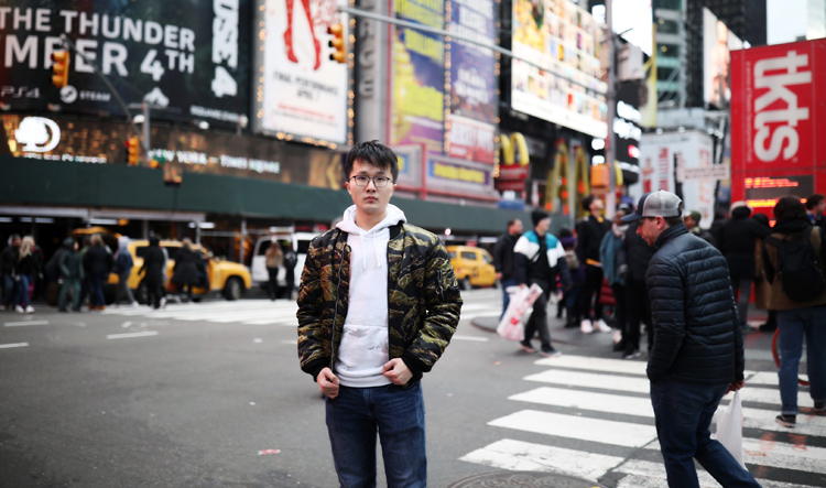 Student Haonan Duan poses at a busy intersection
