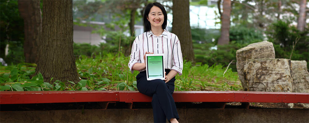 photo of Professor Xi He with her book, Differential Privacy for Databases