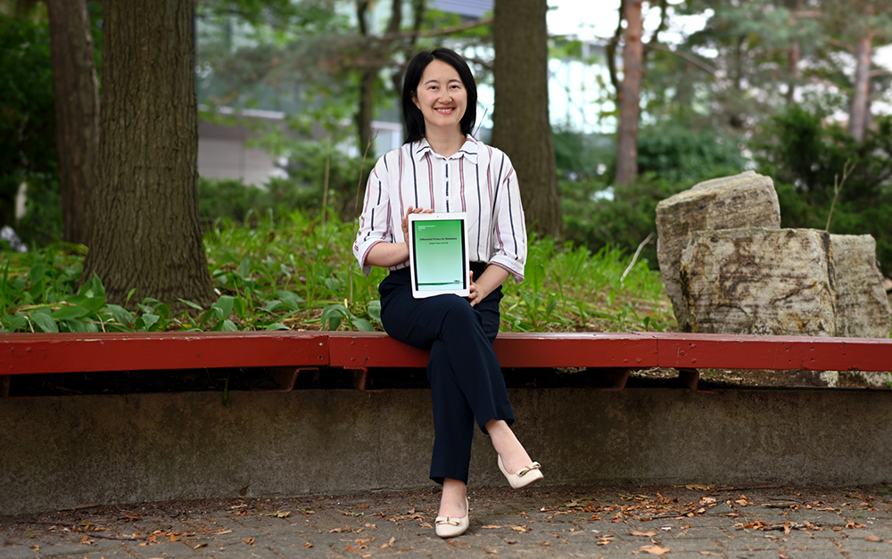 Professor Xi He with her book, Differential Privacy for Databases