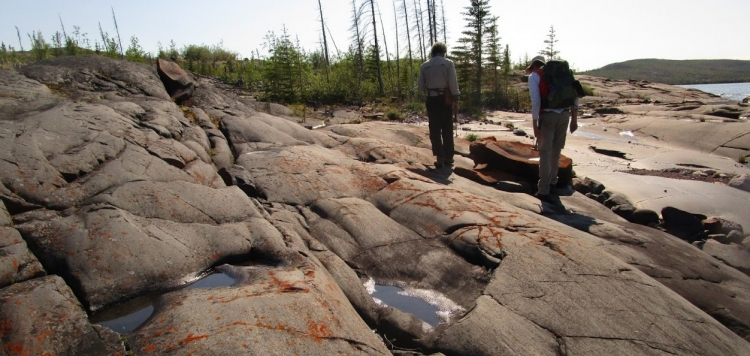 Two students exploring a rock outcrop in Northern Ontario