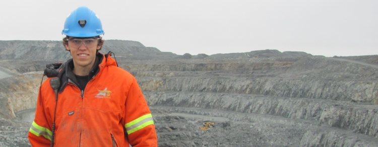 Coop student in front of open pit mine at Agnico Eagle Mine site