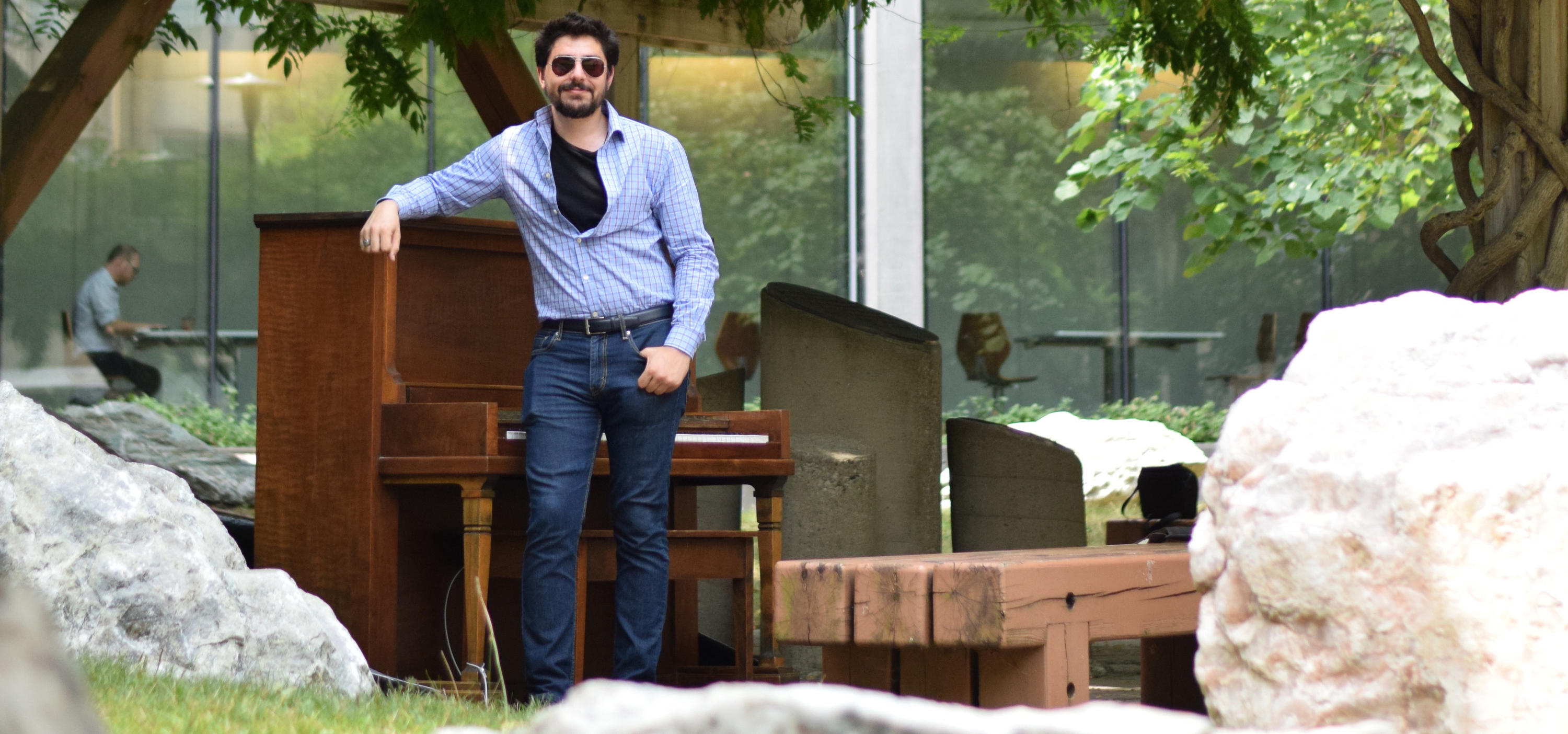 Max Salman stands in front of the latest open piano located in the Peter Russell Rock Garden.