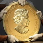 gold coin being held by gloved hands
