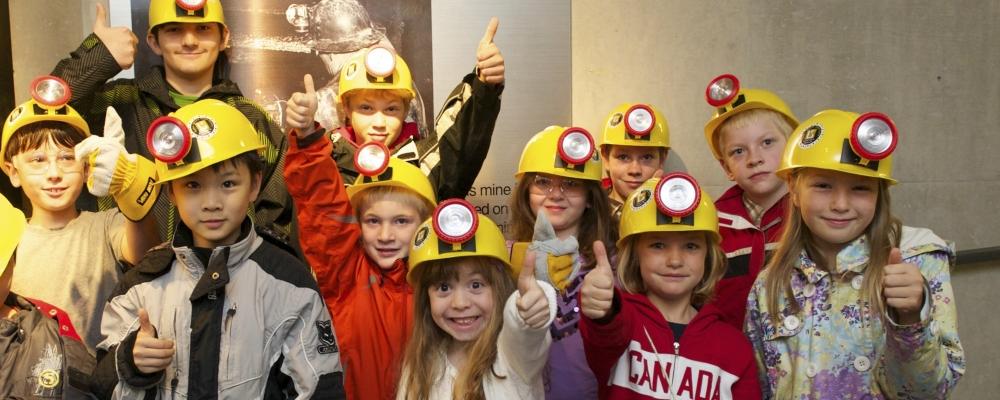 Children with hard hats entering the Cobalt Mine Tunnel.