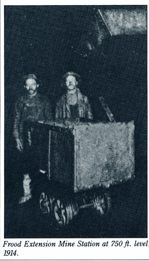 two miners standing with mine cart in dark mine tunnel