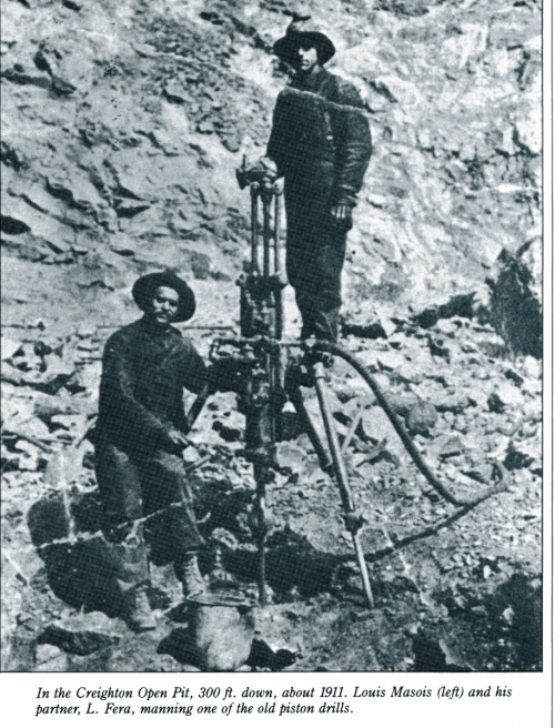 two men operating a piston drill on the surface of an open pit that is 300 feet down