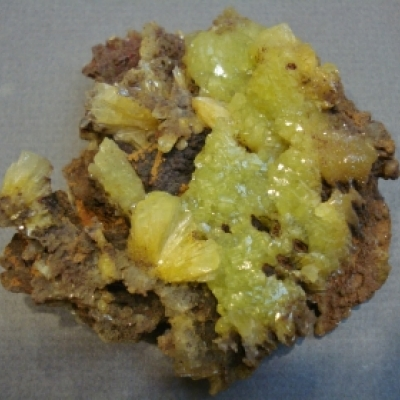 Yellow- green coloured mineral with brown rock or mineral