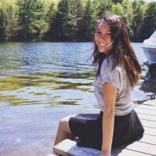 Emma Buczolits sitting on a dock