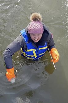 Keana taking water sample while standing in Laurel Creek
