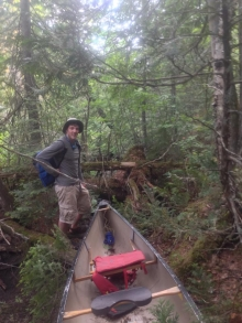 Stephen adventuring through the woods with his canoe