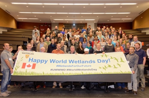 Large group of people holding World Wetlands Day Banner