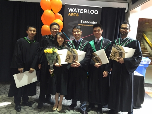 Economics Masters graduates in front of banner