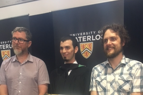 Professors Phil Curry and Jean Guillaume Forand congratulate Tyler