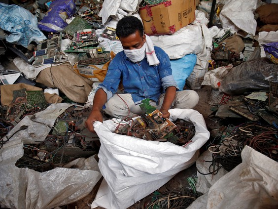 A scrap dealer sorts dismantled TV circuit boards at a scrap yard in Ahmedabad, India, July 2, 2020.
