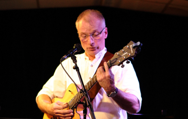 Lutz performing on stage with his guitar
