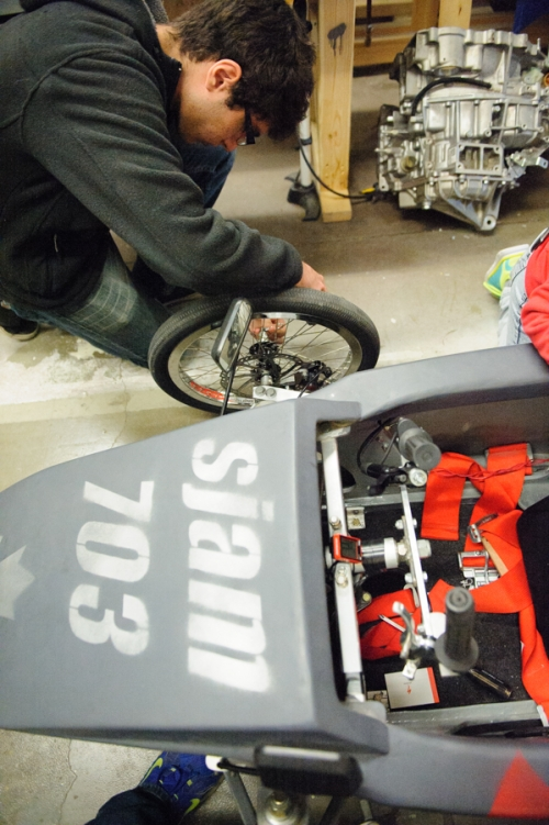 SJAM car club student - Gunes puts cotter pin through axle