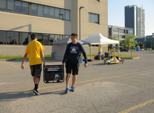 Two team members carrying a generator
