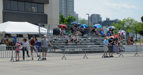 Spectators line the bleachers and railing