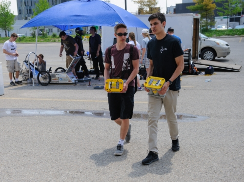 Students carry two fresh 12 V batteries to their car