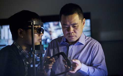 Professor Zhou Wang holding glasses with student