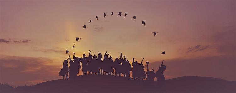 students throwing graduation caps in the air