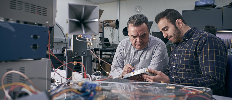 A professor and grad student work on wireless communication hardware in a lab.