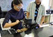 Student unscrewing engine cap.