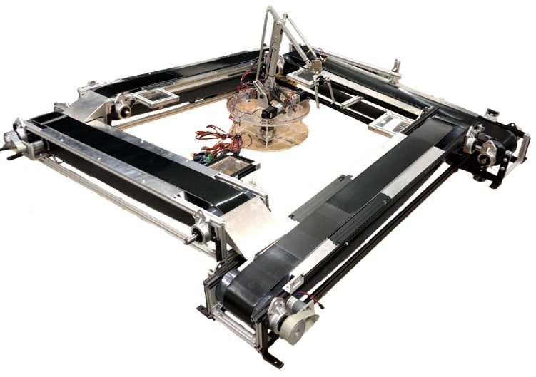 Picture of 4 belted conveyors in a square with a robotic arm in the centre.