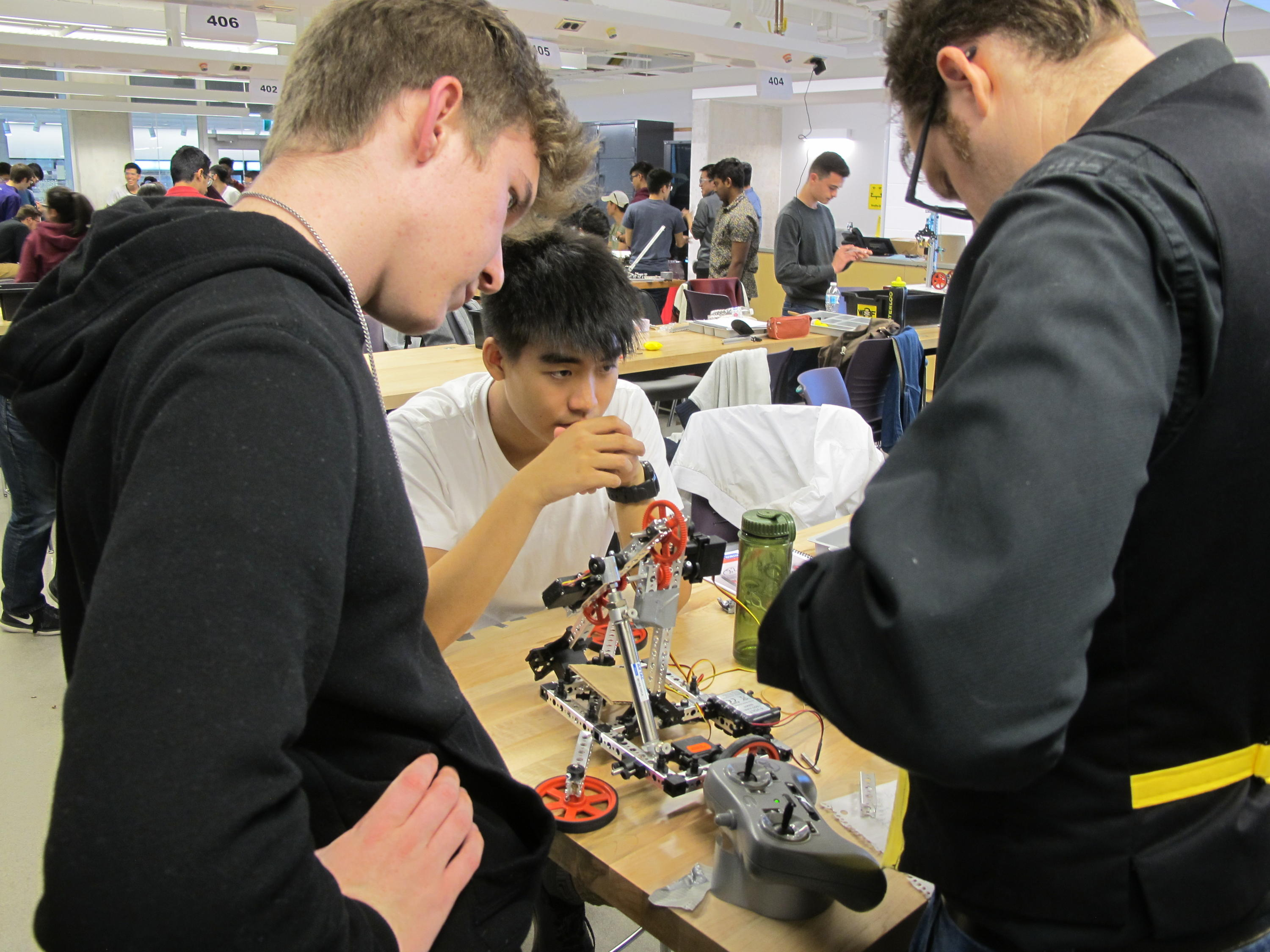 Students working with a tutor on their robotic arm.