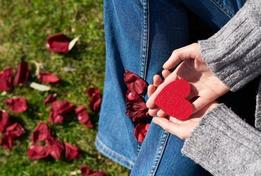 picture of a person's hands and feet. hand is holding a red, felt heart