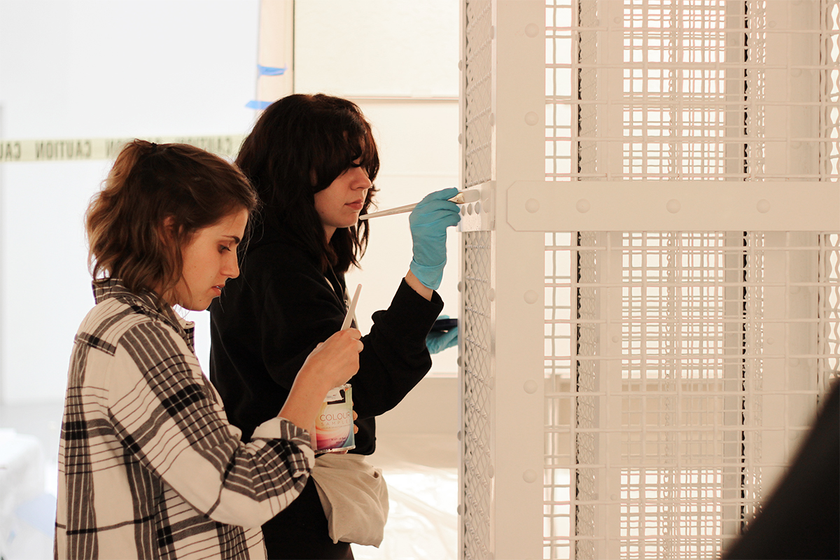 Piper Bernbaum, right, and Anna Longrigg touch up paint on the model gas column of The Evidence Room exhibit