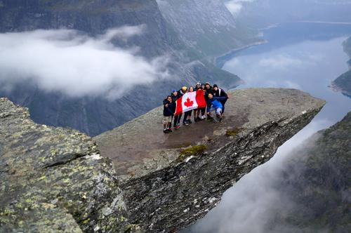 Students holding Canadian flag on a mountain in Norway