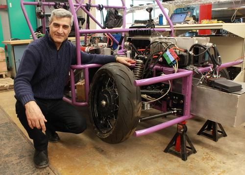 Amir Khajepour poses with a protype three-wheeled vehicle that uses new wheel units developed by Waterloo Engineering researchers.