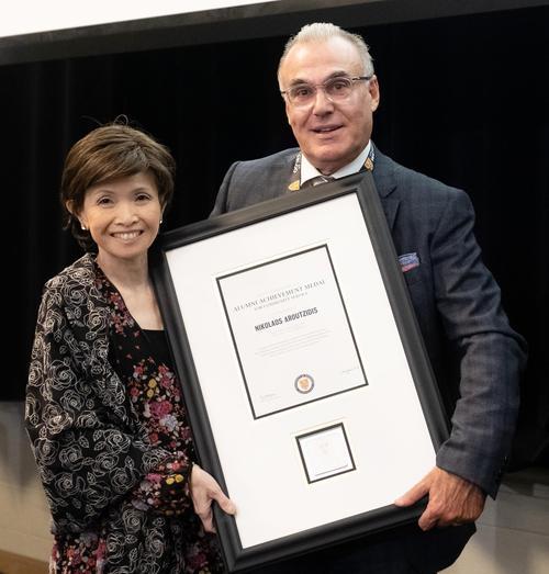 Dean Pearl Sullivan, left, presents the Alumni Achievement Medal in Community Service to Nick Aroutzidis.