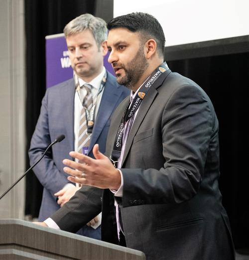 Aman Thind addresses the audience at Federation Hall while Brian Courtney, his partner at Convai Medical, looks on.