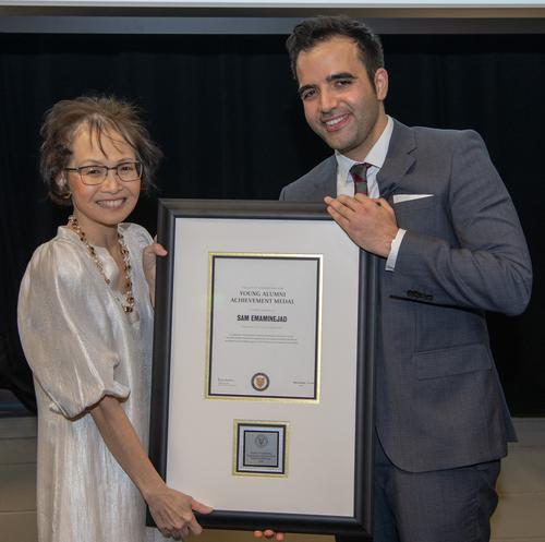 Sam Emaminejad (right) poses with Dean Pearl Sullivan with his award for achievement by young alumni. by