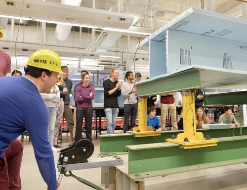 Civil engineering students test bridges made out of styrofoam during an event in the Engineering Ideas Clinic in the new Engineering 7 building.