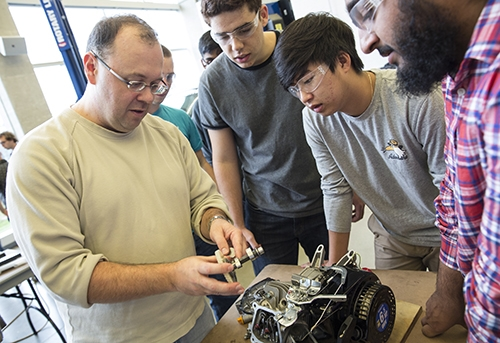 Students examining engine components