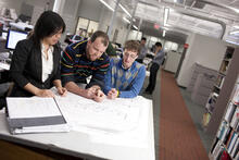 Professor and students working on a floorplan