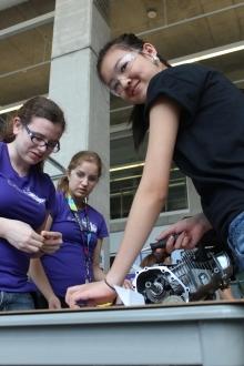 Girls taking apart an engine