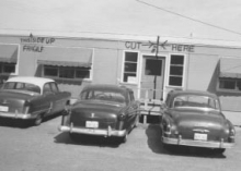 Fifties era cars parked in front of a portable classroom with a large dotted line marking with the label 'Cut here'