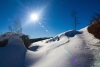 sun shining on snowy hill