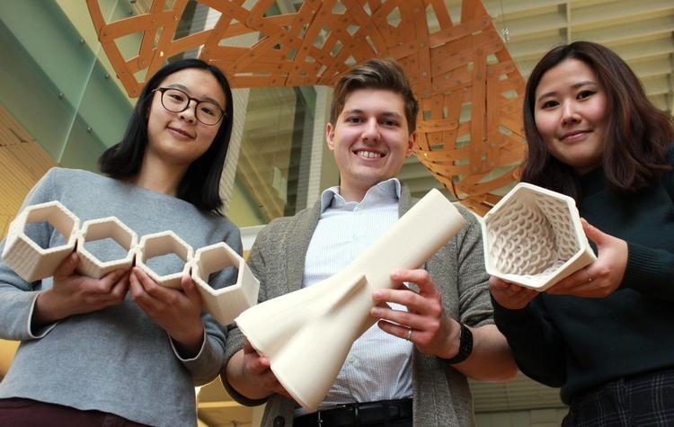 Graduate students Joanne Yau (left to right), Victor Tulceanu and Yesul (Elly) Cho show off the bricks they made out of clay using a new 3D printer at the School of Architecture.