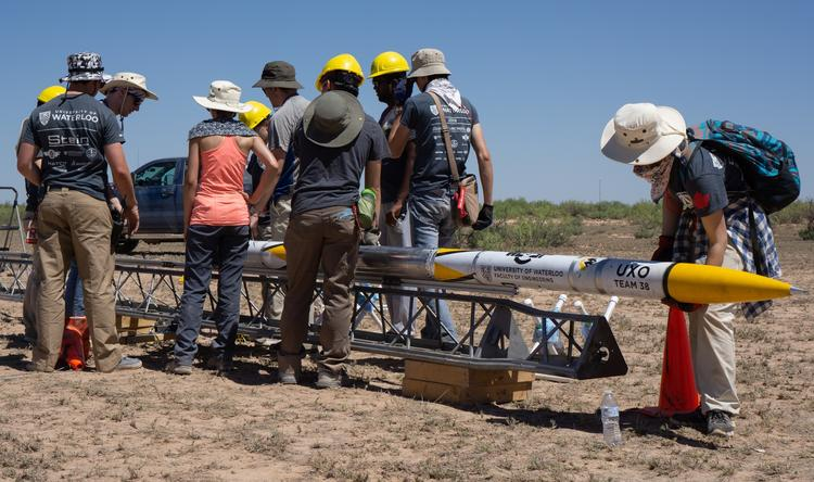 Members of a Waterloo Engineering student design team prepare to launch their new rocket, Unexploded Ordnance (UXO), during a recent competition in New Mexico, where they finished first in their category.