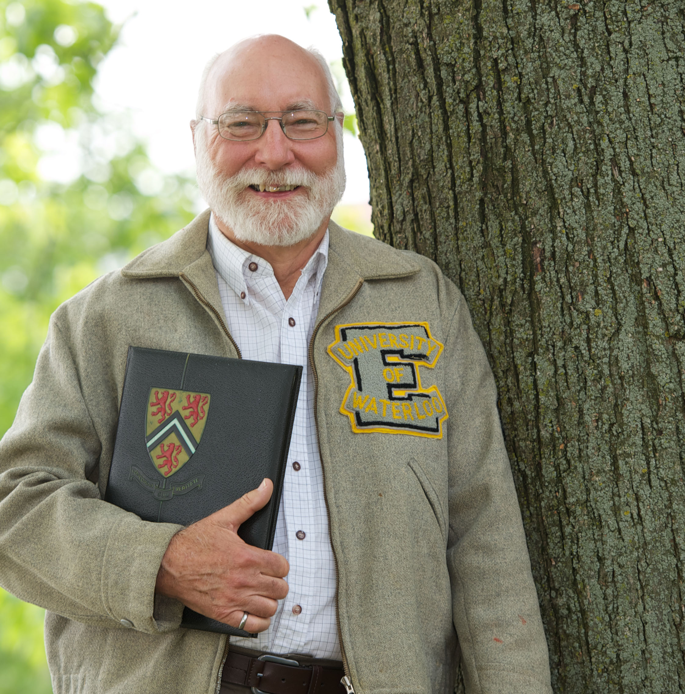 Bill Lennox (BASc '62) wearing Waterloo Engineering jacket and holding yearbook