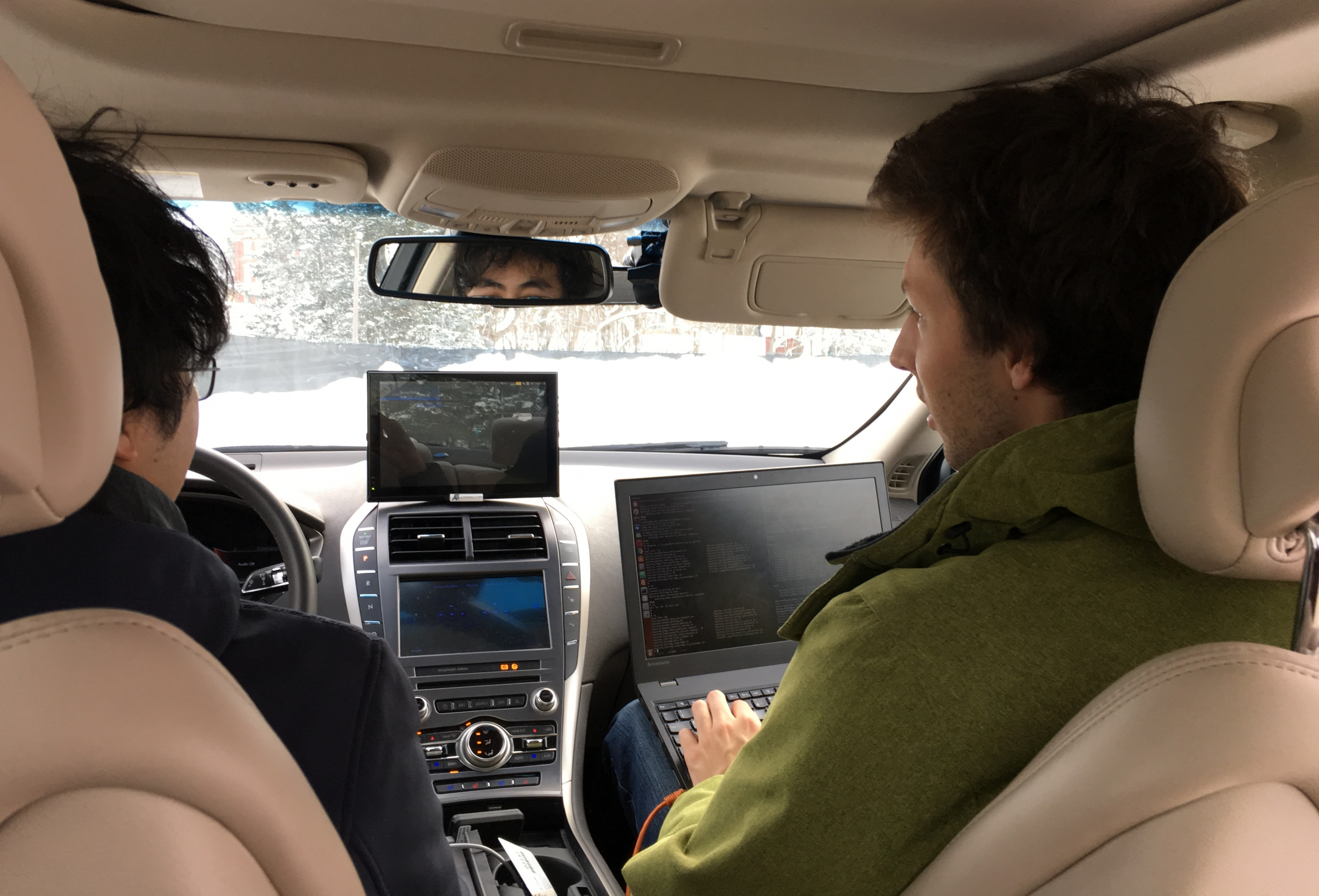 Graduate student researchers Carlos Wang (left) and Ian Colwell track operation of the Renesas sedan during testing in Stratford