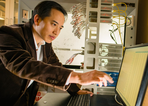 Zhongwei Chen pointing at laptop screen in a research lab
