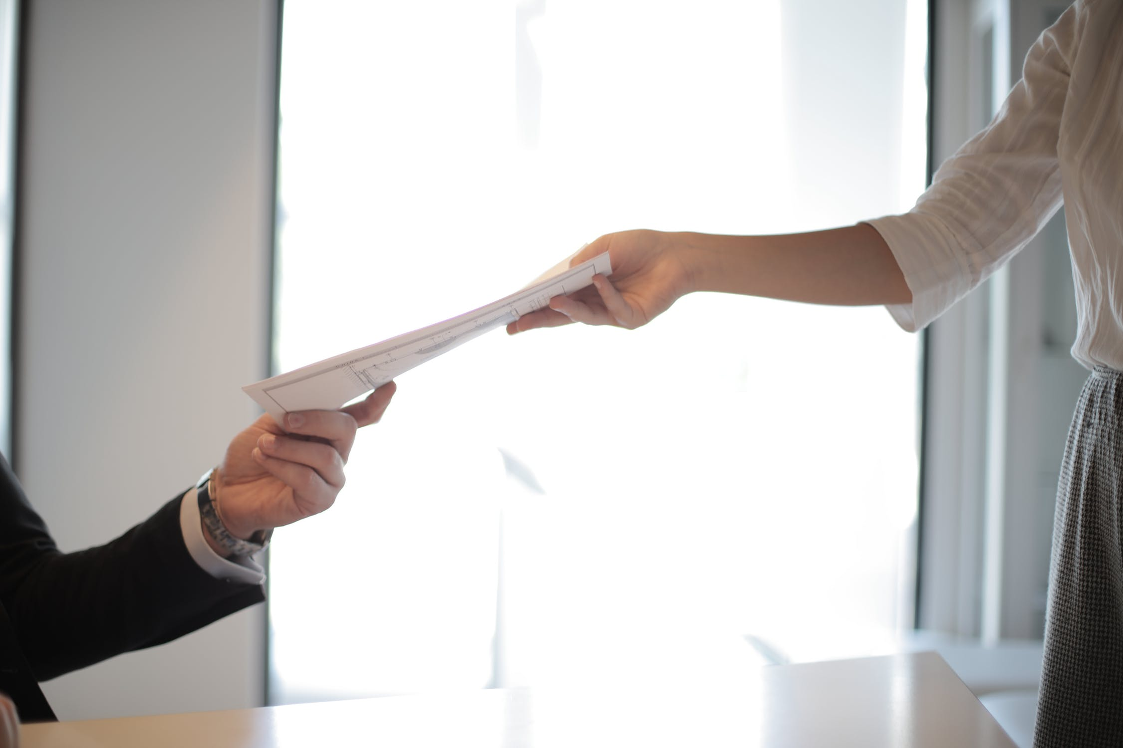 Hand handing resume to another hand