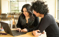 Ceci and Geisson looking at a laptop